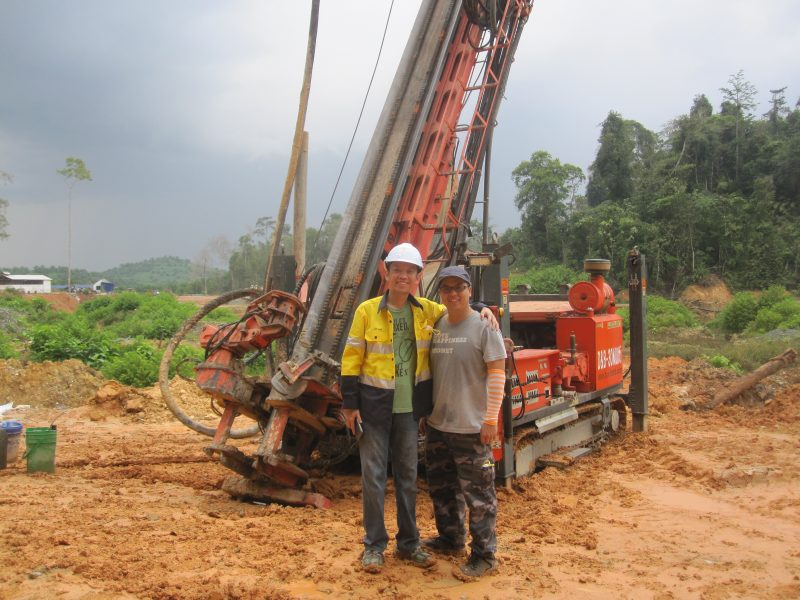 Two miners standing in front of drilling equipment