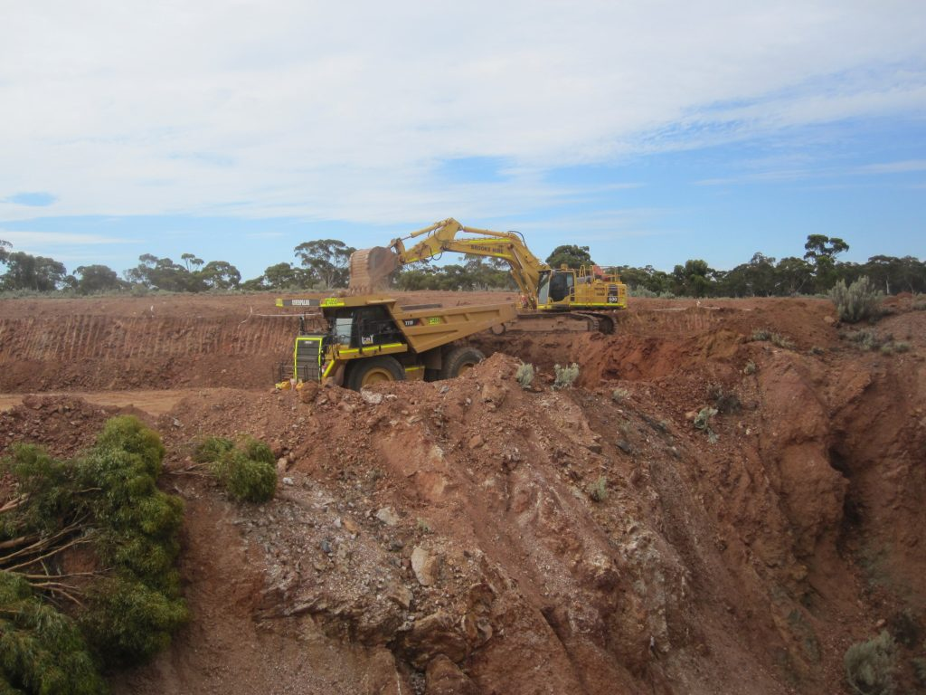 Digger emptying scoop into truck at mine site